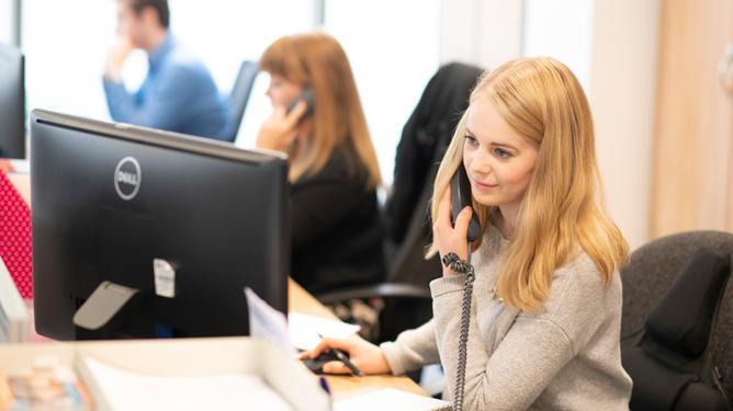 Three members of the MDUK helpline team taking phone calls.