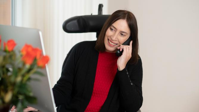 A woman who has FSHD and uses a wheelchair smiles while on the phone as she sits in front of a computer screen.