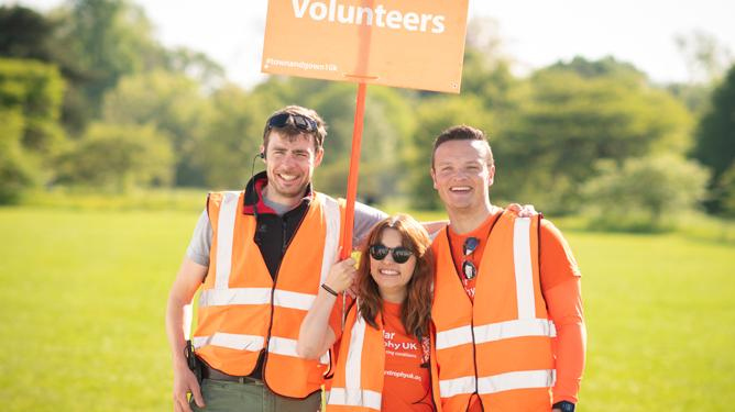 Three MDUK volunteers standing together with a sign saying 'Volunteers' at the Oxford Town & Gown.