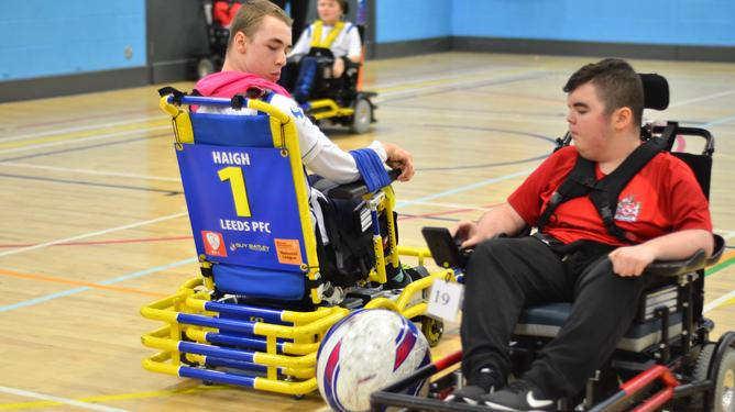 Two wheelchair football players both lock on eyes on the ball between them.