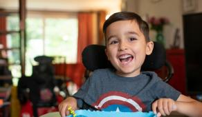 A young boy who has SMA smiles while sat in his wheelchair