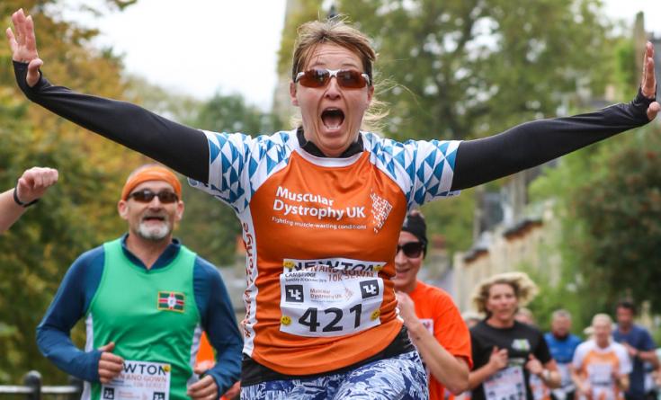 #TeamOrange runner jumping for joy at running event