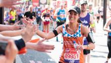 MDUK runner Louisa Hill high fives spectators while running the Virgin London Marathon
