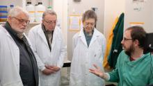 A seated researcher in a green lab coat in discussion with three colleagues wearing white lab coats.