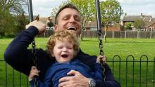 A toddler diagnosed with Congenital Muscular Dystrophy laughing with his dad while the sit together on a swing.